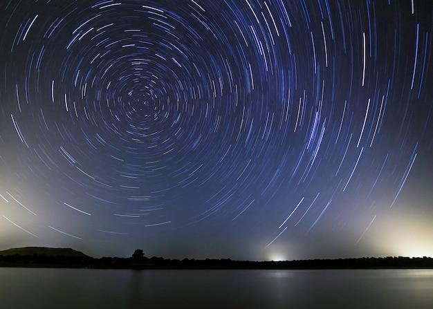 Hemel met een spoor van sterren die draaien op de poolster die aangeeft in welke richting het noorden zich bevindt op een mijnboortoren.