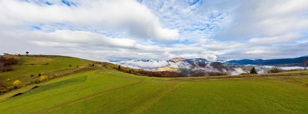 Hemel met witte en pluizige laag wolken over groene herfst heuvels