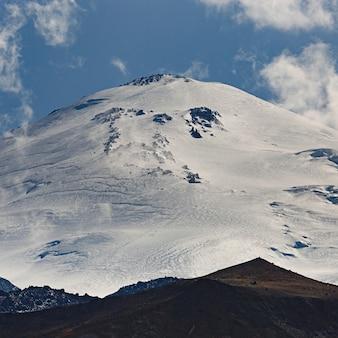 Hemel met wolken boven de besneeuwde top van de elbroes, noord-kaukasus
