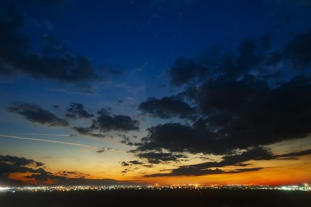 Hemel met wolken na zonsondergang over de stad met straatlantaarn.