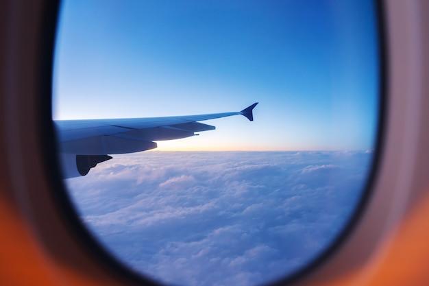 Hemel met zonsondergang vanuit vliegtuigvenster