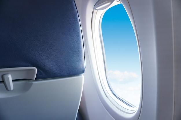 Hemelsblauw of azuurblauwe lucht en wolken vanuit raam van vliegtuig
