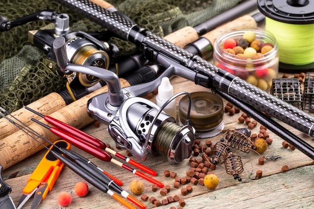 Hengels en spinnings in de samenstelling met accessoires voor het vissen op het oude oppervlak op de tafel