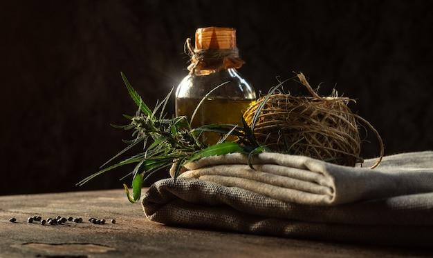 Hennep productconcept. fles olie, textiel, touw en cannabisplant op een houten tafel.
