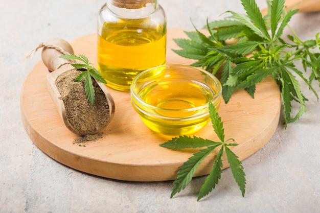 Hennepmeel in houten lepel en etherische olie van hennep. kopieer ruimte. cbd-cannabis.