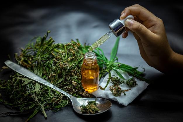 Hennepolie en cannabisbladeren op een donkere ondergrond