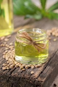 Hennepolie in glazen pot en korrels van cannabis op oude houten plank, fles met olie en bladeren zijn wazig.