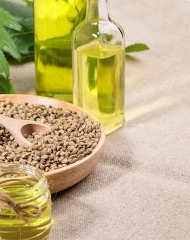 Hennepproducten: olie in glazen pot en fles, cannabiskorrels in ronde houten plaat op jute servet.