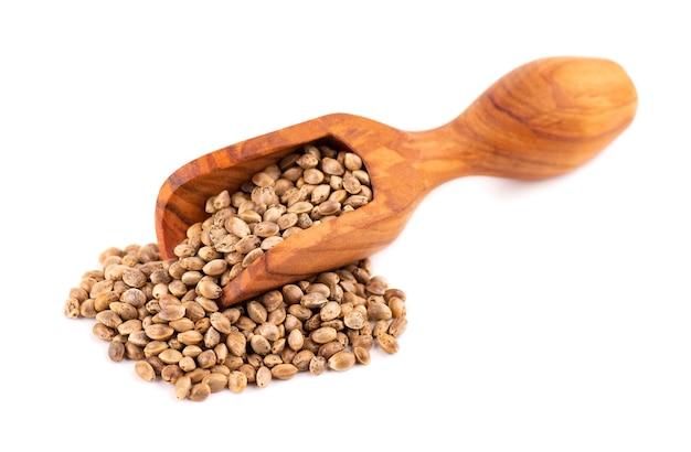 Hennepzaden geïsoleerd. droge zaden van cannabis, hennep of marihuana in houten schep.