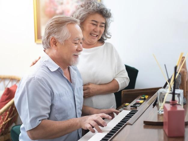 Herbehandeling oudere aziatische grootmoeder en grootvader spelen piano met liefde moment thuis.