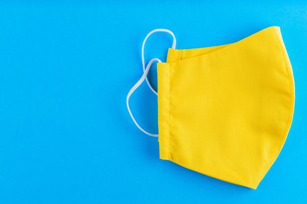 Herbruikbaar gezichtsmasker gemaakt van geel katoen