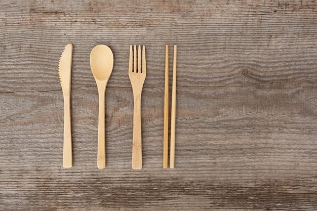 Herbruikbaar houten bestek. eco-vriendelijke vork, mes, lepel, stokken op een oud hout