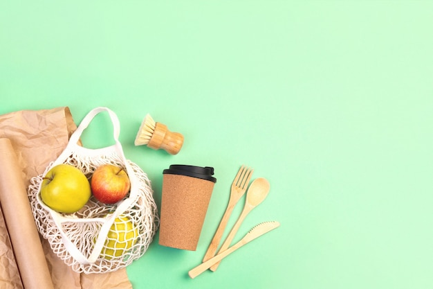 Herbruikbaar houten bestek, kurken mok en boodschappentas met appels. afwasborstel en kraftpapier, milieuvriendelijke vork, mes, lepel op groene muntachtergrond. geen afvalconcept. kopieerruimte.