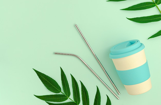Herbruikbare bamboe eco beker met siliconen houder en metalen rietjes op groen