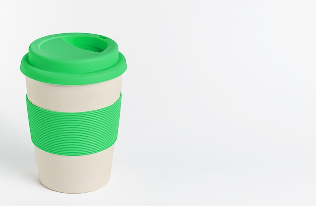 Herbruikbare bamboe koffiekop met groene siliconen houder en deksel op witte muur. geen afval, kopieer ruimte
