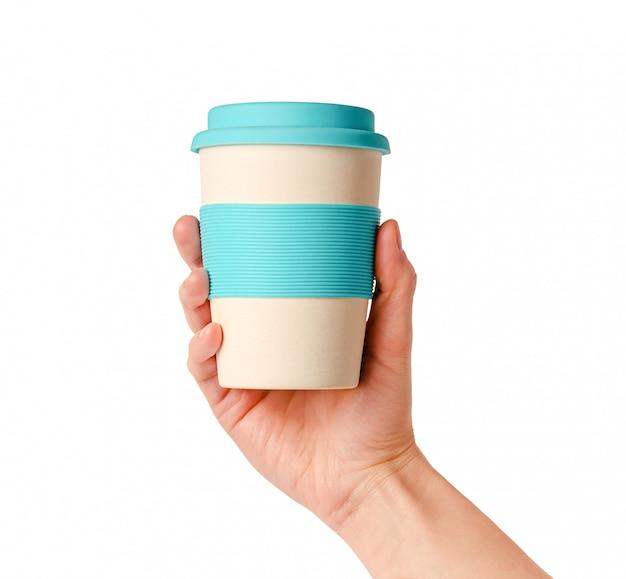 Herbruikbare bamboe koffiekop met siliconen houder in vrouwelijke hand. op wit wordt geïsoleerd. levensstijl zonder afval.