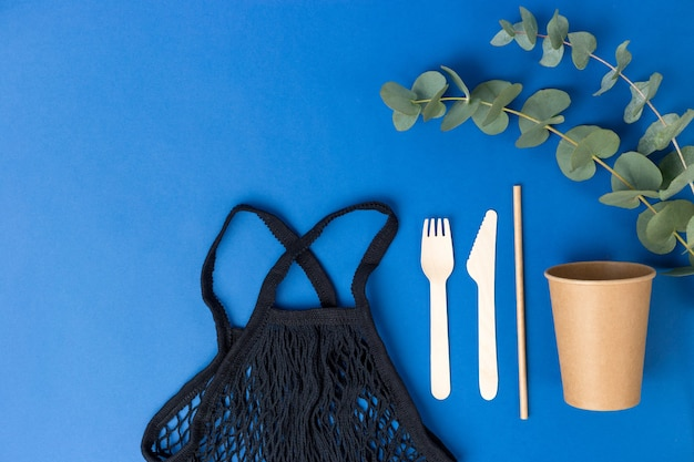 Herbruikbare boodschappentas en eucalyptusbladeren op blauwe achtergrond.