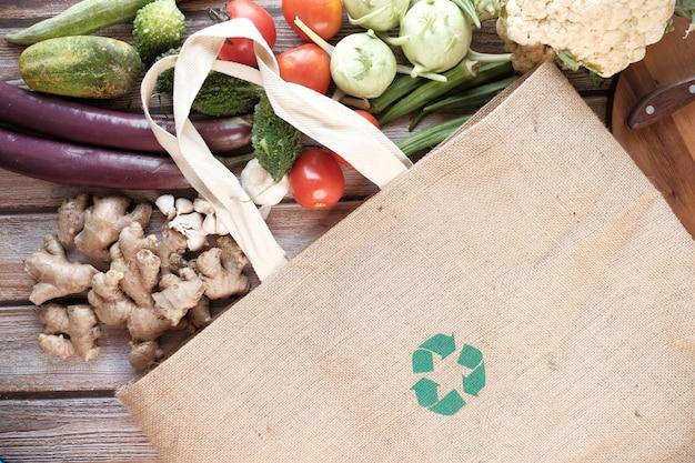 Herbruikbare boodschappentas met gerecycled pijlteken en groenten op tafel