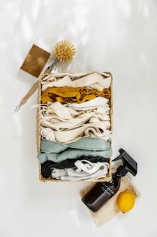 Herbruikbare boodschappentassen en ingrediënten voor eco huis schoonmaken op witte achtergrond.