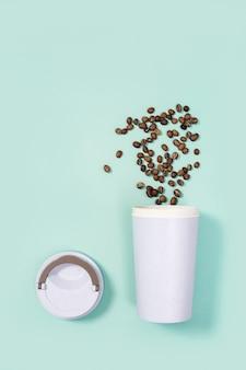 Herbruikbare eco koffiekop met gebrande koffiebonen.
