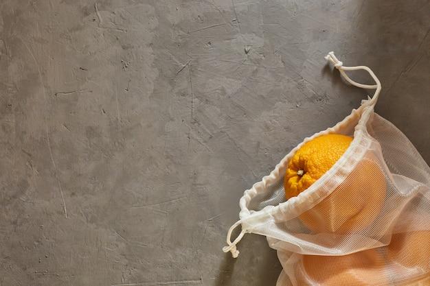 Herbruikbare eco-tas met sinaasappels op een concrete achtergrond. copyspace.