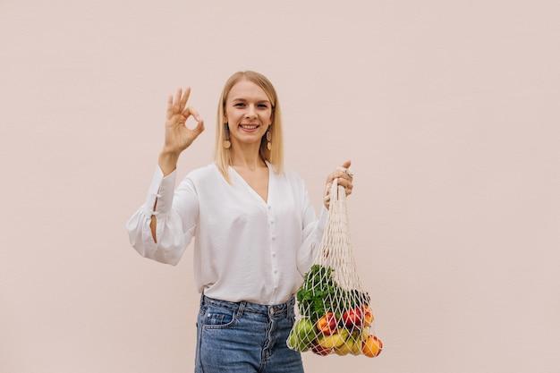 Herbruikbare eco-tas om in te winkelen. jonge vrouw met string boodschappentas met fruit en ok gebaar maakt