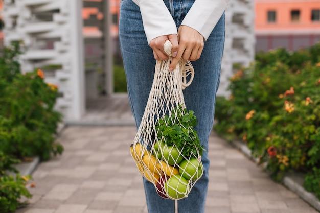 Herbruikbare eco-tas om te winkelen. string boodschappentas met fruit in de handen van een jonge vrouw. geen afval, plasticvrij concept. eco-levensstijl. eco-winkelen. bewuste consumptie. eco-trend.kopieer ruimte