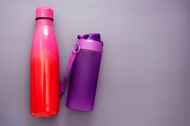 Herbruikbare flessen water over grijze tafel, drinkwater.