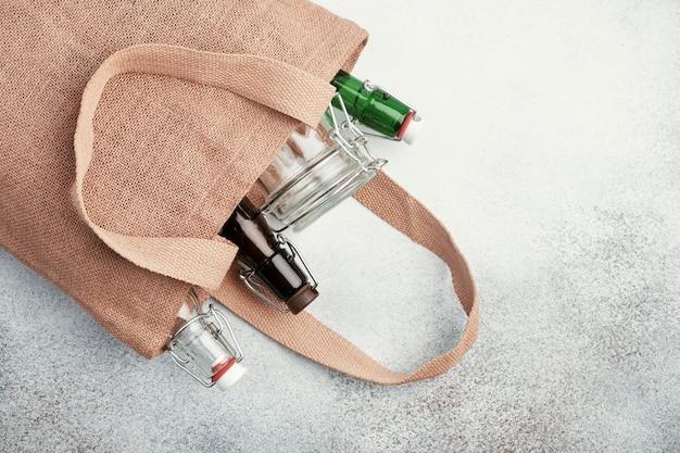 Herbruikbare glazen flessen en potten in jute zak. duurzame levensstijl.