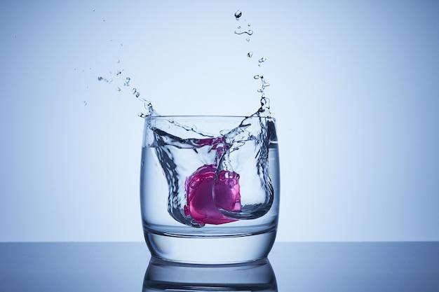Herbruikbare koelblokjes vallen in een glas water of alcohol met spetters en druppels. geïsoleerd ijs verdunt geen water, sappen of dranken.