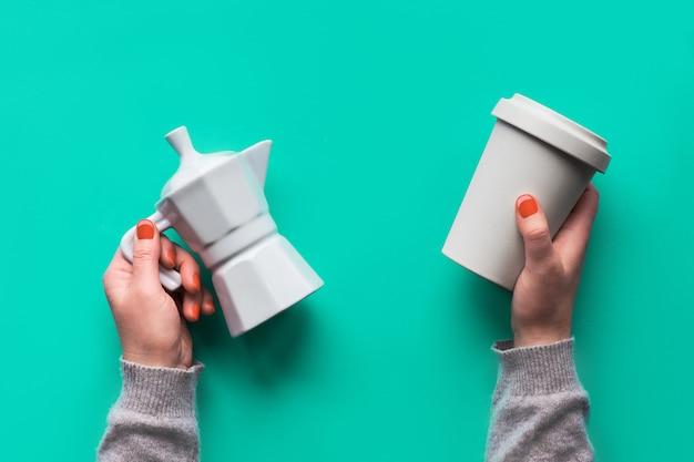 Herbruikbare koffiemok of houd de beker en het witte keramische koffiezetapparaat in handen van de vrouw op een mintgroene muur. creatief platliggend, bovenaanzicht, trendy zero waste-concept, herbruikbare koffiekop met siliconen deksel.