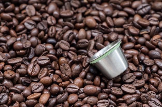 Herbruikbare metalen koffiecapsule op de donker gebrande koffieboon.
