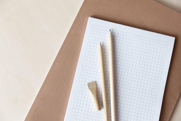 Herbruikbare, milieuvriendelijke pen en potlood voor knutselpapier op het notitieboekje. het schrijven van balpen, milieubescherming, ecologie, natuurlijke materialen, recyclingconcept