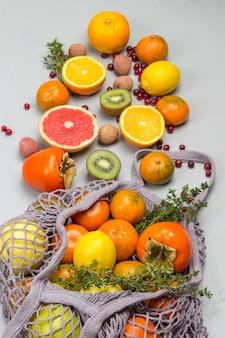 Herbruikbare netzak met fruit. mandarijnen, grapefruit, kiwi, druiven en snijbiet bladeren op tafel.
