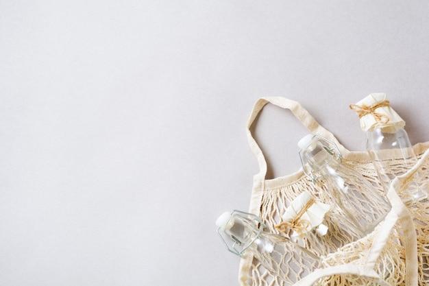 Herbruikbare netzak of mesh shopper en glazen pot op grijs papier