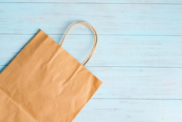 Herbruikbare papieren eco-tassen voor het winkelen van verse natuurlijke producten op een houten lichtblauwe achtergrond.