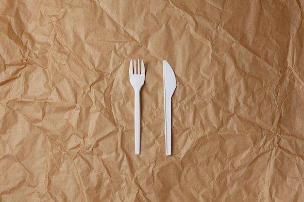 Herbruikbare recyclebare witte vork, mes gemaakt van maïs of haverzetmeel op bruin verfrommeld kraftpapier, kopieerruimte