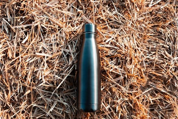 Herbruikbare stalen thermo waterfles op achtergrond van droge hooiberg.