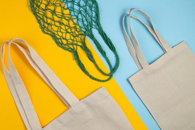 Herbruikbare stoffen tas op een gekleurde achtergrond. bovenaanzicht plat lag kopie ruimte