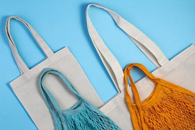 Herbruikbare textiel tas op blauwe achtergrond. bovenaanzicht plat lag kopie ruimte.
