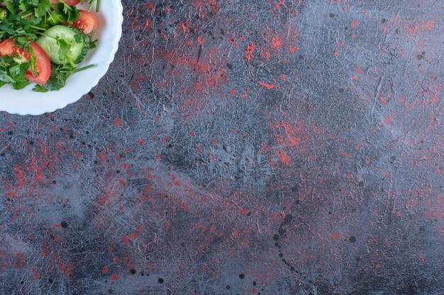 Herderssalade gemengd met peterselieblaadjes op zwarte tafel.