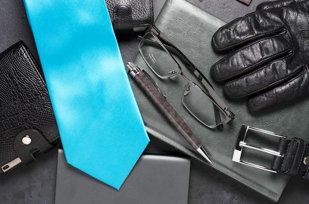 Heren accessoires en kleding op een zwarte betonnen tafel