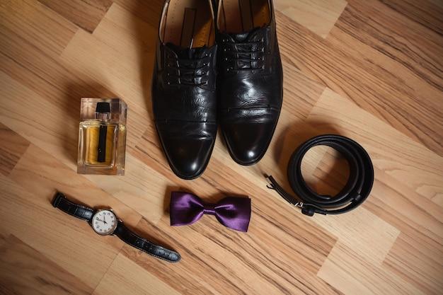 Heren accessoires op houten achtergrond. schoenen, vlinderdas, riem en polshorloge voor zakenman.