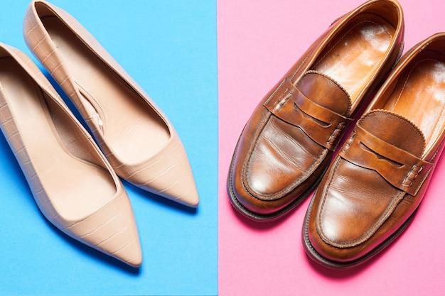 Heren- en damesschoenen op een blauwe en roze kleurrijke achtergrond. zakelijke werkschoenen met kopieerruimte plat leggen. bovenaanzicht