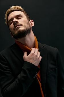 Heren in een jas oranje trui gebaren met zijn handen blond donker