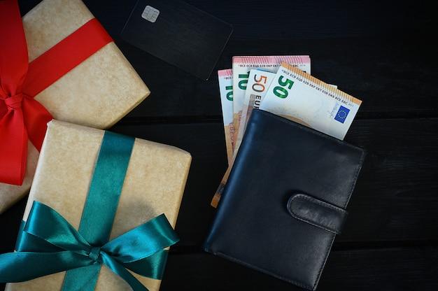 Heren lederen portemonnee met euro, op zwarte tafel met geschenkdozen