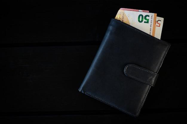 Heren lederen portemonnee met euro, op zwarte tafel