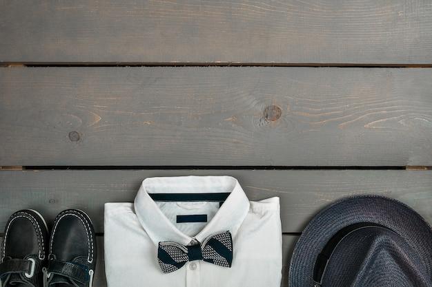 Heren outfit op houten achtergrond, kindermode kleding, grijze fedora, wit overhemd, bootschoenen voor jongen, bovenaanzicht, plat leggen, kopie ruimte.