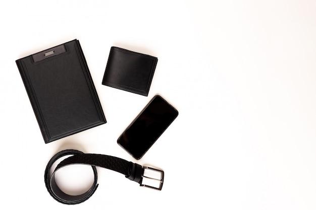 Heren set. totaal zwart. zwart lederen dagboek, zwart lederen riem, zwart lederen portemonnee en telefoon op een witte achtergrond. uitzicht van boven.