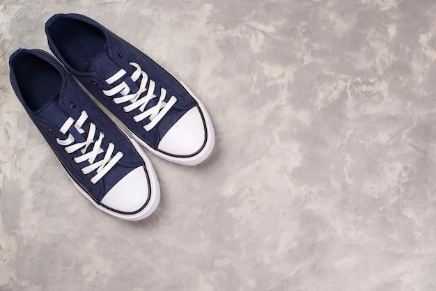 Heren sneakers in donkerblauwe dikke stof, bovenaanzicht. hipster schoenen op een moderne betonnen grijze achtergrond.